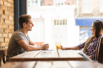 Young couple chatting in bar