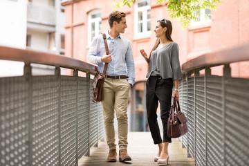 Businessman and woman walking and talking on footbridge, London, UK