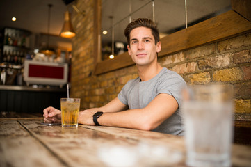 Young man at table in city bar