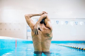 Rear view of male swimmer stretching at swimming pool