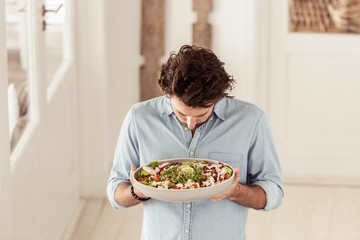 Man holding serving dish of salad looking down