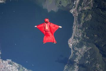 Wingsuit skydiver pilot flying over lake, Locarno, Tessin, Switzerland