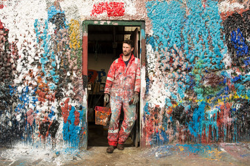 Man in dirty workwear standing at colorful wall