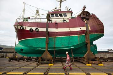 Worker walking in front of ship in shipyard