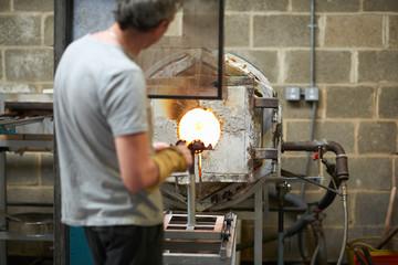 Glassblower in workshop using furnace