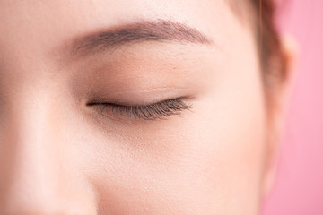 Beautiful asian woman eye with long eyelashes isolated on pink b
