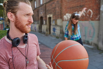 Young couple outdoors, throwing basketball