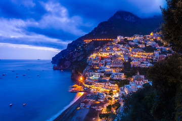 Cliff side buildings illuminated at night, Positano, Amalfi Coast, Italy
