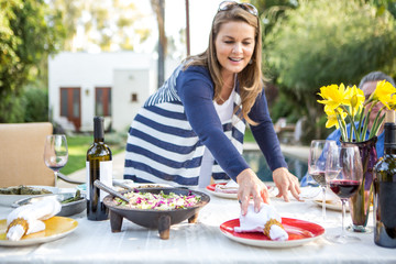 Mature woman placing napkins on garden party table