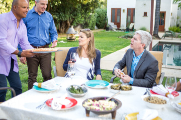 Mature man serving fish cuisine talking at garden party table