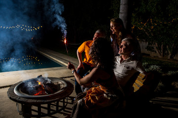 Mature adult couples watching sparkler by patio fire at night