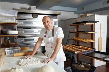 Portrait of male baker preparing dough
