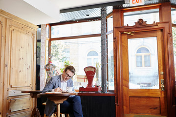 Man sitting in cafe, writing in notebook