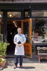 Portrait of male worker, standing outside bakery