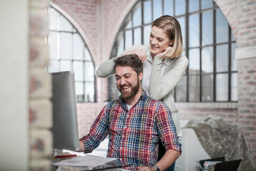 Couple at home, using computer, laughing