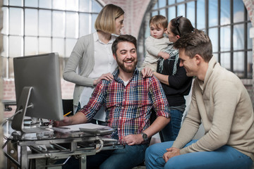 Group of adults sitting around computer having discussion, woman holding toddler behind them