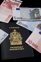Canadian passport and euros on black background