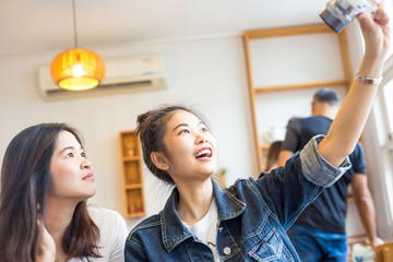 Portrait of two happy young Asian woman take selfie in cozy coff