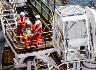 Engineers in brainstorming session on oil rig