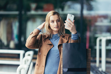 Beautiful, fashionable, young woman with shopping bags smiling and taking selfie with her cell phone. Outdoor city street portrait.