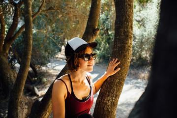 Woman wearing baseball cap and sunglasses sitting in tree