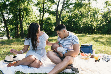 Parents cradling baby son on picnic blanket in Pelham Bay Park, Bronx, New York, USA