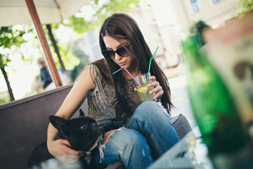 Cute teenager girl enjoying outdoors in cafe bar playing with her adorable French bulldog puppy. Strong back light. Warm sunny day.