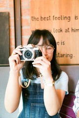 Portrait of fashionable asian young glasses photographer with vi