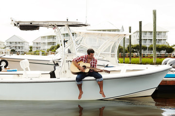 Young man playing acoustic guitar on motorboat in marina