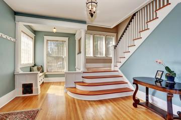 Hallway interior in blue tones, columns and hardwood floor. View of stairs.