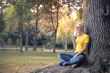 Blonde woman drinking at the park