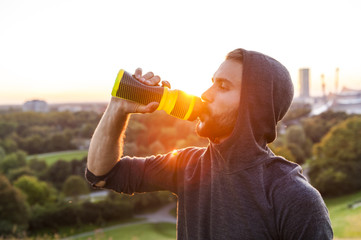 Athlete drinking from bottle at sunset