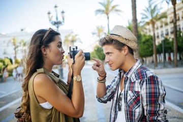 Spain, Jerez de la Frontera, young woman taking picture of her boyfriend