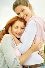 Portrait of two cuddling happy women