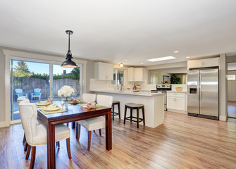 Open floor plan dining area with elegant table setting and white soft chairs.