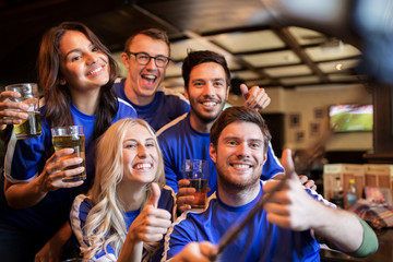 football fans with beer taking selfie at pub