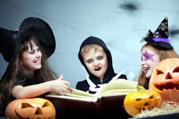 Three little children in Halloween fancy dresses sitting and reading a book