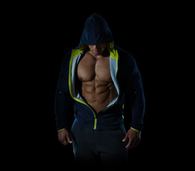 Creative muscle athletic man in a jacket with a hood, abdominal on black background