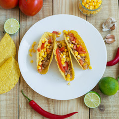 Square photo of three crispy tacos with chicken meat, corn and tomato on a white plate and ingredients on wooden background