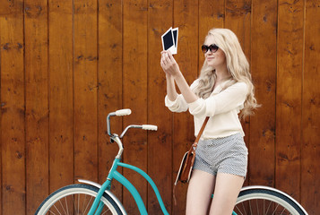 sexy blond wyoung oman standing near a green vintage bicycle holding photos and smiling, warm, tonning