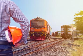 engineer holding safety helmet with orange diesel engine locomotive passenger train background