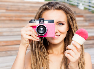 Beautiful young woman with dreadlocks taking photos with vintage pink retro film camera and pink ice-cream have fun in warm summer evening
