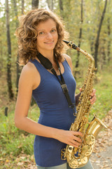 Beautiful girl in a blue t-shirt playing the saxophone in gold o
