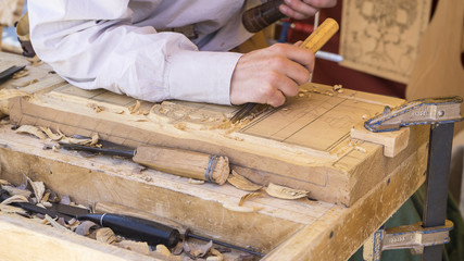 craftsman carving wood in a medieval fair, carpentry tools