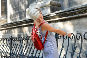 Fashionable portrait of a young short haired beautiful woman in grey sexy evening dress with red leather backpack purse.  Fashion model. Trendy blonde hipster girl having fun on a sunny day.