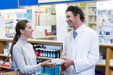 Pharmacist assisting the pills to customer
