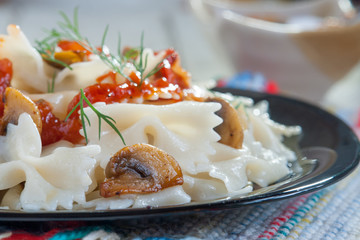 Farfalle Pasta with mushrooms on white plate and tomato sauce