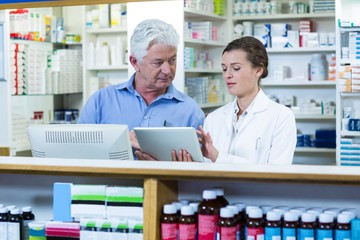 Pharmacists using digital tablet at counter