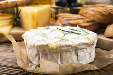 Camembert with rosemary on a wooden board