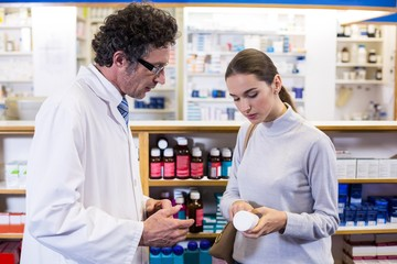 Pharmacist assisting the bottle of drug to customer